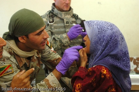 Iraqi Army Pvt. Ahmed Abdualsuda, a medic with the 2nd Brigade, 9th Iraqi Army Division (Mechanized) examines a little girl's mouth which is causing her pain at a school set up as a make-shift clinic during a combined medical effort near Bassam, Iraq Sept. 27.  Photo Credit: Oct 1, 2007