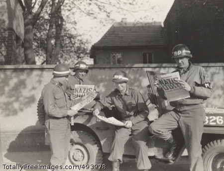 """Nazi's Quit"" Four MP's take a break along a German road to read in the 'Stars and Stripes' newspaper about the Nazi surrender. Nelson A. Shuey Photograph Collection.