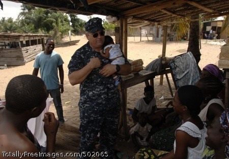 110407-N-HI707-825 LAGOS, Nigeria (April 7, 2011) Capt. Lawrence Rollo cradles a Nigerian baby while visiting with locals during a community relations project at the Light of Dawn Government Junior Secondary School Tomarow as part of Africa Partnership Station (APS) West. APS is an international security cooperation initiative designed to strengthen global maritime partnerships through training and collaborative activities to improve maritime safety and security in Africa. (U.S. Navy photo by Mass Communication Specialist 1st Class Darryl Wood/Released)