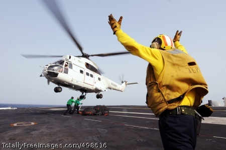 110625-N-XE109-350 GULF OF ADEN (June 25, 2011) Aviation Boatswain's Mate (Handling) 1st Class Jerome Gaynor signals a 330J Puma helicopter as Sailors attach cargo nets during a vertical replenishment aboard the aircraft carrier USS George H.W. Bush (CVN 77). George H.W. Bush is deployed supporting maritime security operations and theater security cooperation efforts in the U.S. 5th Fleet area of responsibility on its first operational deployment. (U.S. Navy photo by Mass Communication Specialist Seaman Apprentice Brian Read Castillo/Released)
