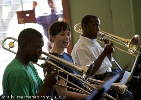 110420-N-RM525-033 KINGSTON, Jamaica (April 20, 2011) Musician 3rd Class Loralee Swanson, from Rapid City, S.D., listens as trombone players from the Alpha Boys School concert band play a song during a Continuing Promise 2011 subject matter expert exchange at the Alpha Boys School. Continuing Promise is a five-month humanitarian assistance mission to the Caribbean, Central and South America. (U.S. Navy photo by Mass Communication Specialist 2nd Class Jonathen E. Davis/Released)