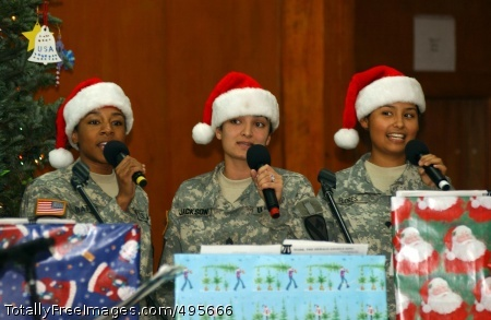 Holiday spirit (From left) Sgt. Alison Bates, Sgt. LeAnne Jackson and Spc. Veronica Flores sing a Christmas melody for Soldiers at Camp Liberty, Iraq, Dec. 23. The singing group, 'Minority Report,' is part of the 1st Cavalry Division Band. Photo Credit: Dec 26, 2006
