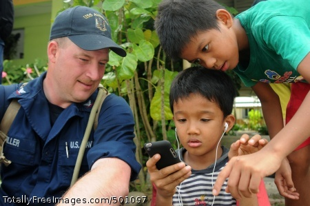 110506-N-SP676-176 KOTA KINABALU, Malaysia (May 6, 2011) Mineman 3rd Class Matt Miller, assigned to the mine and countermeasures ship USS Avenger (MCM 1), gives children his smart phone to play with at the Bukit Harapan home for disabled and disadvantaged children in Kota Kinabalu. (U.S. Navy photo by Mass Communication Specialist 3rd Class Brian A. Stone/Released)