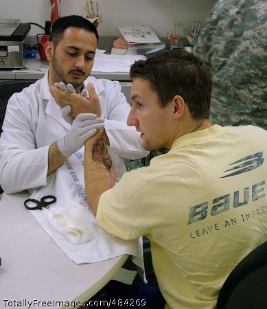 WRAMC: Providing Occupational therapist Hector Romero works with Staff Sgt. Jonathan Kearns following Kearns' skin-graft surgery at WRAMC. Kearns was shot in Afghanistan while deployed with the 3rd Special Forces Group.  Photo Credit: Jun 27, 2008