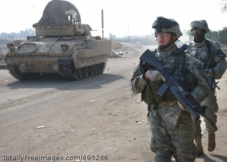 Soldiers Free Spcs. Eloy Pena and Gregory Guyton, from the 1st Cavalry Division, move to their Bradley fighting vehicle during a combined cordon and search mission in Ghazaliya, Iraq.  Photo Credit: Jan 29, 2007