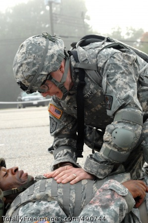 Reassuring Care Competitor Staff Sgt. Russell Burnham, U.S. Army Medical Command, keeps a wounded Soldier calm and asks questions about his wounds in order to perform combat first aid during the Warrior Tasks and Battle Drills event, Oct. 4, in the Department of the Army NCO/Soldier of the Year Competition at Fort Lee, Va.' Photo Credit: Oct 4, 2007