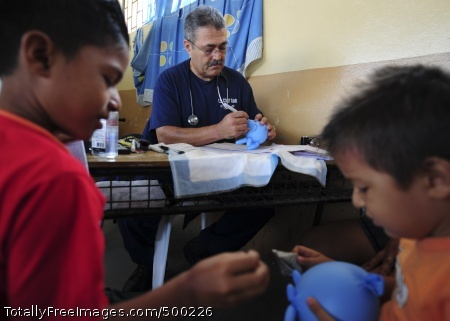 110523-N-QD416-239 MANTA, Ecuador (May 23, 2011) Capt. Jose Sanchez makes an elephant out of a pair of surgical gloves for two young patients at a clinic near Manta, Ecuador, during Continuing Promise 2011. Continuing Promise is a five-month humanitarian assistance mission to the Caribbean, Central and South America. (U.S. Navy photo by Mass Communication Specialist 1st Class Brian A. Goyak/Released)