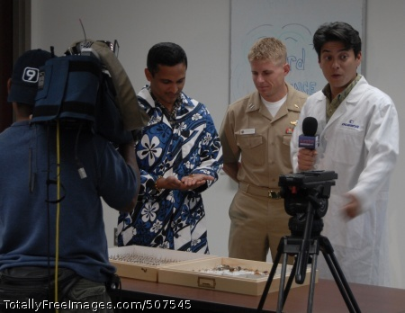 101109-N-2198T-010 PEARL HARBOR (Nov. 9, 2010) A film crew from Hawaii News Now records Lt. Bryan Heintschel, center, assigned to Navy Environmental and Preventive Medicine Unit 6, explaining to Dr. Vinod Veedu, right, and Taizo Braden the proper technique for pinning and classifying insects. Veedu is the host of Weird Science with Dr. V., a children's show promoting science and technology. (U.S. Navy photo by Lt. j.g. Casey Two Bears/Released)
