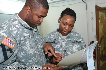 Staff Sgt. Rosie Threatt, senior Human Resources noncommissioned officer for the 1st Air Cavalry Brigade, 1st Cavalry Division, (right), discusses personnel actions with New Orleans native Spc. Troy Halley, Human Resources information specialist, (left), Nov. 19 at Camp Taji, Iraq. Threatt, a Port Gibson, Miss., native, joined the Army in 1999 to get a college education and make a better life for her family. Photo Credit: Nov 27, 2007