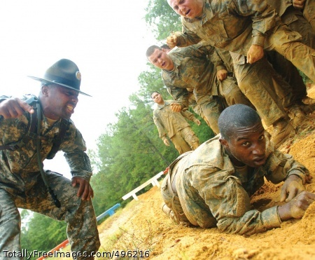 Basic Training Sgt. Primus Brown, a drill sergeant, and recruits offer words of encouragement to a trainee negotiating the obstacle course at Fort Benning, Ga. This photo appeared on www.army.mil. Photo Credit: Oct 23, 2006