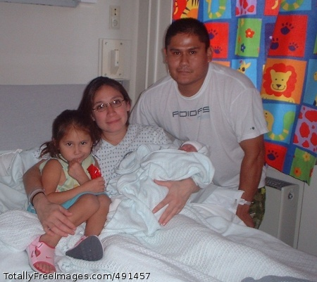 Family from Angelina Day holds her newborn daughter, Isabella, alongside her husband, Army Staff Sgt. Leonard Day, and their daughter, Esperanza, at Landstuhl Regional Medical Center, Germany, where Sergeant Day is recuperating from wounds received from an improvised explosive device while deployed to Afghanistan. Photo Credit: Sep 17, 2007