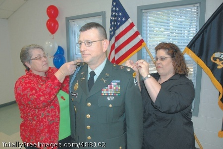 Returning to the Newly promoted Lt. Col. Richard MacDermott, executive officer, Task Force Marshall, has his new rank insignia pinned on by his wife Patricia (left) and his daughter Jennifer Moss during a promotion ceremony Friday at McCrady Training Area. MacDermott has gone from a second lieutenant to major, from major to sergeant, from sergeant to sergeant first class, from sergeant first back to major to his new rank Photo Credit: Feb 12, 2008