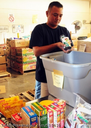 110302-N-KT462-113 HONOLULU, Hawaii (March 2, 2011) Culinary Specialist 1st Class Raymund Lee, assigned to Joint Base Pearl Harbor-Hickam, checks expiration dates on nonperishable goods at the Hawaii Food Bank. Service members who volunteered at the food bank prepared food for distribution to those in need. (U.S. Navy photo by Mass Communication Specialist 2nd Class Jon Dasbach/Released)
