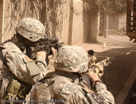 Covering Their Sgt. Karl King and Pfc. David Valenzuela lay down cover fire while their squad maneuvers down a street from behind the cover of a Stryker combat vehicle to engage gunmen who fired on their convoy in Al Doura, Iraq, March 7.  The Soldiers are from Company C, 5th Battalion, 20th Infantry Regiment, 3rd Brigade Combat Team, 2nd Infantry Division. Photo Credit: Mar 19, 2007