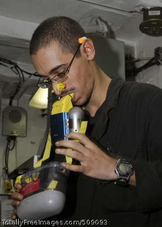 100927-N-3729D-096 ARABIAN SEA (Sept. 27, 2010) Machinist's Mate Fireman Aleric Hernandez dons an emergency escape breathing device while inside main control of the aft main machinery room during engineering training evolutions aboard the amphibious assault ship USS Peleliu (LHA 5). Peleliu is the command ship of the Peleliu Amphibious Ready Group supporting maritime security operations and theater security cooperation efforts in the U.S. 5th Fleet area of responsibility. (U.S Navy photo by Mass Communication Specialist 2nd Class Andrew Dunlap/Released)
