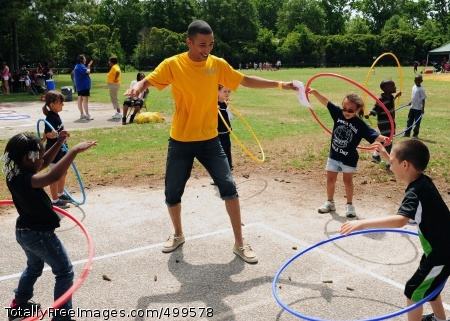 110603-N-ED149-266 NORFOLK (June 3, 2011) Yeoman 3rd Class Trevor W. Hunnicutt, assigned to the aircraft carrier USS Theodore Roosevelt (CVN 71), shows students how to hula hoop during a field day at Sewell's Point Elementary School. The field day is Sewell's Point's closing event for the school year. (U.S. Navy photo by Mass Communication Specialist Seaman Apprentice Andrew Lester N. Sulayao/Released)