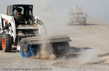 Street sweeper Staff Sgt. William Parker, from the 19th Engineer Battalion, brushes up the streets of Muqdadiyah, Iraq, Dec. 22. His S150 Bobcat loader removes dirt covering previous mine holes, which will be filled with cement to make the route passable. Photo Credit: Jan 9, 2007