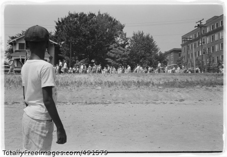 Little Rock, 1959. Photograph shows a young African American boy watching a group of people, some carrying American flags, march past to protest the admission of the 'Little Rock Nine' to Central High School.  Library of Congress Prints and Photographs Division Washington, D.C. 20540 USA  Photo Credit: Sep 12, 2007