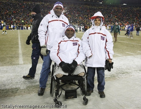 Wounded Warrior Lt. Col. Greg Gadson (center), an honorary team captain for the N.Y. Giants, is shown here with his son Jaelen and Hall of Fame Linebacker Harry Carson during the National Football Conference Championship game Jan. 20 at Lambeau Field in Green Bay, Wisc.  Photo Credit: Feb 4, 2008