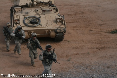 Bradley fighting Soldiers from the 2nd Combined Arms Battalion, 5th Brigade (Army Evaluation Task Force) 1st Armored Division, run towards their objective after dismounting from a Bradley tank fighting vehicle.    Photo Credit: Sep 27, 2007