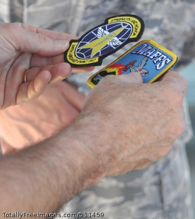 ETERSON AIR FORCE BASE, Colo. – Navy Adm. James A. Winnefeld, Jr., holds both the 34th Aeromedical Evacuation Squadron and the 302nd Airlift Wing's Modular Airborne Firefighting System patches in his hand after being presented them from 302nd AW leadership July 26 at Peterson Air Force Base, Colo. Winnefeld, commander of the North American Aerospace Defense Command and U.S. Northern Command, together with senior leaders from both organizations, visited the Air Force Reserve's 302nd AW to gain a better understanding of the specialized missions the AF Reserve supports, to include aeromedical evacuation and aerial firefighting. The visit also showcased the capabilities Air Force Reservists can provide to civilian-related missions if called upon.