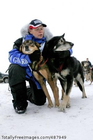 Iditarod Hug Rodney Whaley hugs two of his sled dogs. Photo Credit: Feb 25, 2008