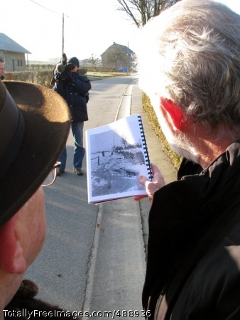 Battle of the Bulge Ted Paluch, left, a survivor of the 1944 Malmedy massacre of 84 U.S. Soldiers in Belgium, compares a photo taken of the scene then and how the area looks now. Photo Credit: Dec 21, 2007
