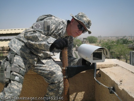 New Surveillance Sgt. 1st Class Mark Henderson, operations NCO with the Army's Rapid Equipping Force, installs a new surveillance system on Camp Victory, Baghdad. The system is called the Rapid Deployment Integrated Surveillance System, or RDISS.  Photo Credit: Jul 27, 2007