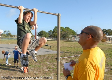 101130-N-5523J-005 JACKSONVILLE, Fla. (Nov. 30, 2010) Electricians Mate 1st Class Claude Troullier coaches a student from the fourth grade class at San Pablo Elementary School on pull-ups. Sailors assigned to Naval Station Mayport are volunteering at the school to prepare children in achieving the Presidential Fitness Award. (U.S. Navy photo by Aviation Electricians Mate 3rd Class Omari Janhrette/Released)