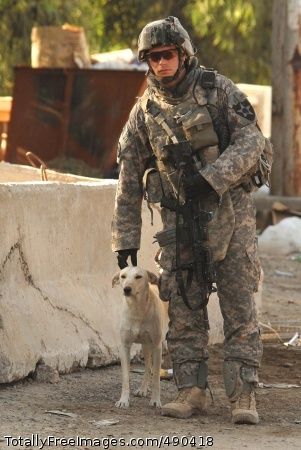 The Dogs of War Sgt. Justin Silverthorn, from Company C, 4th Battalion, 9th Infantry Regiment, 4th Stryker Brigade Combat Team, 2nd Infantry Division, takes a break to pet a stray dog at a U.S. and Iraqi Army security checkpoint in Tarmiyah, Sept. 25.   Photo Credit: Oct 23, 2007