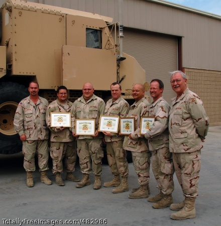 Direct Impact Department of the Army civilian employees of the 401st Army Field Support Brigade's Forward Repair Activity pose with their supervisors after receiving 4th Sustainment Brigade Certificates of Achievement, July 24, 2008, for their work making possible add-on-armor upgrades to M1070 Heavy Equipment Transport Tractors at Camp Arifjan, Kuwait. Pictured (L-R) are supervisor Jacky Austin, Robert Lane, Timothy Holley, Garry Wills, Robert Gregg, Joel McClellan and supervisor Kenneth Higgins, all volunteers who deployed to Southwest Asia from Anniston Army Depot, Anniston, Ala. Not pictured are Lance Jennings, Jared Bussie and Micah Garrett, who have returned to home station.  Photo Credit: Jul 30, 2008