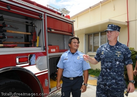 101001-N-1906L-025 SANTA RITA, Guam (Oct. 1, 2010) Capt. Richard Wood, right, commanding officer of U.S. Naval Base Guam (NBG), discusses the features of a new fire truck with Nicholas Perez, fire captain of NBG Ordnance Annex, following a ribbon cutting ceremony. (U.S. Navy photo by Jesse Leon Guerrero/Released)