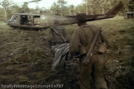 Medevac at LZ X-Ray Soldiers of the 1st Battalion, 7th Cavalry, carry a wounded comrade to a waiting UH-1 of the 229th Assault Helicopter Battalion, during the fight for LZ X-Ray in the Ia Drang Valley of Vietnam.  Photo extracted from US Army motion picture footage. (Nov 1965)' Photo Credit: Feb 26, 2007
