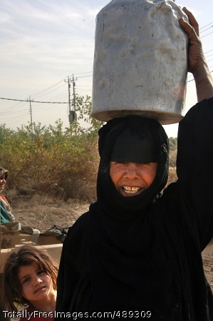Water for Al Buaytha A happy resident carries her water bucket home. Photo Credit: Dec 5, 2007