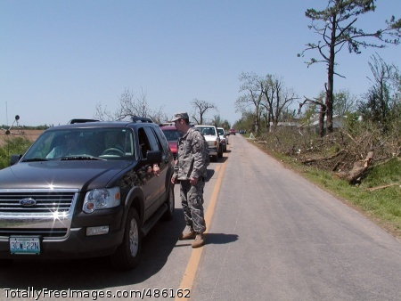 Missouri Guard Spc. Russell Fenno with the Missouri National Guard Forward Support Company, 203rd Engineer Battalion directs traffic around a heavily affected area in Newtonia, Mo., after a tornado destroyed dozens of structures and uprooted hundreds of trees on Saturday. Photo Credit: May 12, 2008