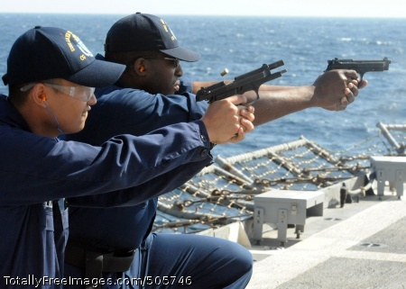 101230-N-3415O-218 ARABIAN SEA (Dec. 30, 2010) Logistics Specialist 2nd Class Alexander Castillo, left, and Information Systems Technician 1st Class Cyrus Fluitt fire M9 service pistols during small arms qualifications aboard the guided-missile cruiser USS Lake Champlain (CG 57). Lake Champlain is deployed with Commander, Task Force 151 supporting maritime security operations and theater security cooperation efforts in the U.S. 5th Fleet area of responsibility. (U.S. Navy photo by Mass Communication Specialist 1st Class Michael O'Day/Released)