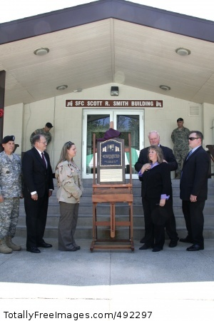 Community dedicates (from left) Command Sgt. Maj. Daniel K. Elder, U.S. Army Materiel Command command sergeant major, James Sutton, deputy program executive officer for ammunition, widow Gari-Lynn Smith, parents Robert and Shirl Smith and brother Shawn Smith unveil the plaque that honors Sgt. 1st Class Scott R. Smith during the dedication of 'The Smith Building' here Tuesday.