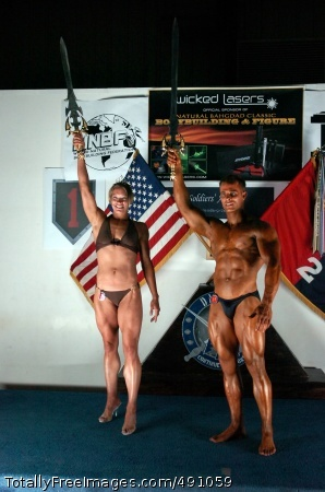 The overall winners of the 2nd Baghdad Classic Bodybuilding and Figure Competition, College Park, Md., native Spc. Allison Schlegel and Staff Sgt. Joseph Fiorani from Eldersburg, Md., both from the 58th Infantry Brigade Combat Team, pose for pictures taken at the conclusion of the 2nd Baghdad Classic Body Building and Figure Competition at the Morale, Welfare and Recreation Field House at Camp Liberty in western Baghdad Sept. 29.  Photo Credit: Oct 2, 2007