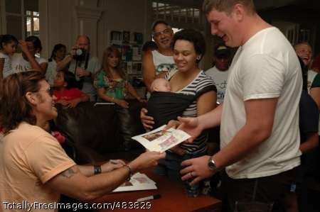 Country superstar SCHOFIELD BARRACKS, Hawaii - Billy Ray Cyrus hands an autographed photo to Spc. Chris Palo, WTB and wife Cynie during the meet and greet at the Warrior Assistance Center during the July 4th festivities. Cyrus met with many wounded warriors and their family members, signing autographs and engaging each in conversation. Photo Credit: Jul 9, 2008
