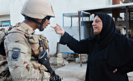 Program Integrates Sgt. Yasser Ahmed, a soldier from the Iraqi Army's 3rd Battalion, 1st Brigade, 11th Infantry Division, talks with a local woman during a patrol in the Graya'at area of Baghdad's Adhamiyah District Sept. 5.  Photo Credit: Sep 20, 2007