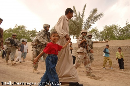 TLC for Iraqi Boy Ayhab and his father are escorted by U.S. and Iraqi soldiers in Narhwan, Oct. 6. The boy will be airlifted to a hospital in Najaf where he will receive colonoscopy reversal surgery. Photo Credit: Oct 25, 2007