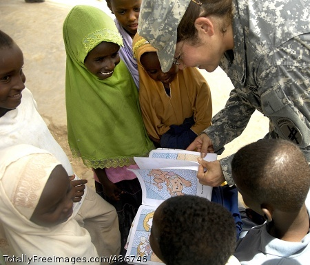 Brightening Their Lt. Col. Elizabeth J. Largeman reads a book to children who are waiting to be seen by Army medical personnel during a medical civil action project in Dammerjog, Djibouti. Servicemembers assigned to Combined Joint Task Force - Horn of Africa provided medical care to more than 500 people in the area during a two-day period this month. Photo Credit: Apr 21, 2008