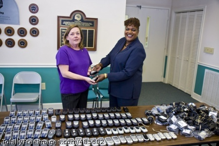 Much-needed Anniston Army Depot Director of Information Management Alberta Freeman (right) is on hand May 19 at the United Way in Anniston, Ala., to officially hand over more than 100 cellular phones to Susan Shipman (left), executive director of 2nd Chance, a non-profit organization that helps victims of domestic violence. 