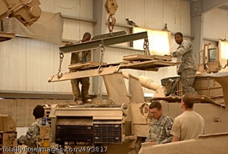 Mechanics Bay Tank mechanics and operators guide the back cover down onto a tank in the mechanics bay at Forward Operating Base Brassfield-Mora near Samarra, Iraq. Photo Credit: Apr 24, 2007