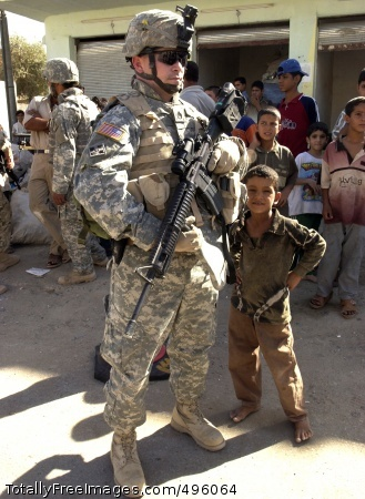 Troop rotations set An Iraqi child stands beside Staff Sgt. Marc Runge as he provides security for his unit, the 67th Armored Regiment, during a presence patrol in Ad Diwaniyah. Photo Credit: Nov 20, 2006