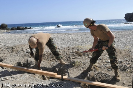 110113-N-3887D-530 GUANTANAMO BAY, Cuba (Jan. 13, 2011) Utilitiesman 1st Class Kevin Geegan, right, and Construction Mechanic 3rd Class Christopher Covas dig a hole to place a bollard at Cable Beach. Both Sailors are assigned to Naval Mobile Construction Battalion (NMCB) 28, which is deployed from Shreveport, La. to Guantanamo Bay supporting general improvement, engineering, construction and project management. (U.S. Navy photo by Mass Communication Specialist 2nd Class Elisha Dawkins/Released)