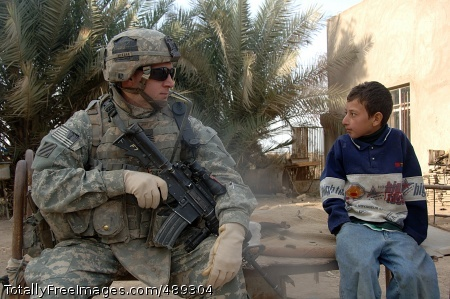 Patrolling Arab Spc. Keith McKern interacts with an Iraqi boy during the dismounted patrol. Photo Credit: Dec 5, 2007