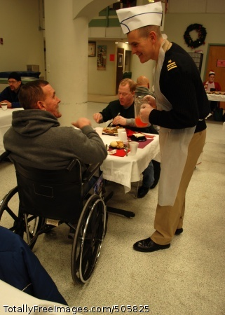 101225-N-7642M-106 BOSTON (Dec. 25, 2010) Lt. Cmdr. Anthony Savage, executive officer of USS Constitution, serves Juice and chats to a veteran at the New England Center for Homeless Veterans during a Christmas dinner visit. Constitution Sailors have volunteered 1,113 man-hours to the center since establishing a partnership in April. (U.S. Navy photo by Mass Communication Specialist 3rd Class Kathryn E. Macdonald/Released)
