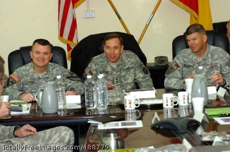 CAMP TAJI, Iraq - Gen. David H. Petraeus (center), commanding general, Multi-National Force- Iraq, Round-up, Mont. native Col. Paul E. Funk II (left), commander, 1st 'Ironhorse' Brigade Combat Team, 1st Cavalry Division and Col. Todd McCaffrey, commander, 2nd Stryker Brigade Combat Team Warriors, 25th Infantry Division attend a briefing in the Ironhorse Brigade conference room at Camp Taji, Iraq Dec. 31. The senior leaders met to discuss the upcoming transfer of authority between the Ironhorse Brigade, which has been in theater for nearly 15 months, and its counterparts in the Warrior Brigade. Photo Credit: Jan 3, 2008
