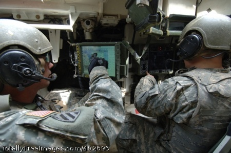 Training in 'Land Staff Sgt. George Adams (left) and Spc. Brenton Steckel monitor the Force XXI Battle Command Brigade-and-Below and Remote Weapons System screens in their Stryker vehicle, while looking for 'enemy contacts.' Photo Credit: Jul 2, 2007